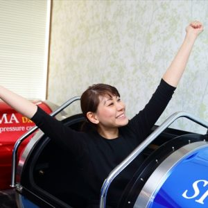 酸素カプセルSIGMA-DXに入ってスッキリしたポーズの女性の画像